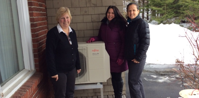 Heather Shuve is proud to be Saint John Energy's first rental program customer, shown here with Jennifer Coughlan and Marta Kelly from Saint John Energy in front of her new Fujitsu compressor.